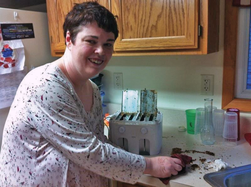 a CILA resident cleaning her kitchen