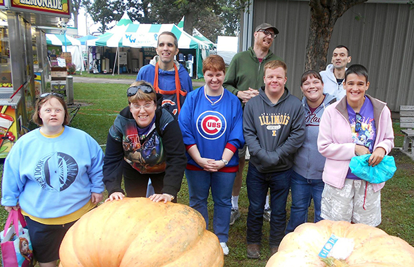 clients posing with giant pumpkins at a fair