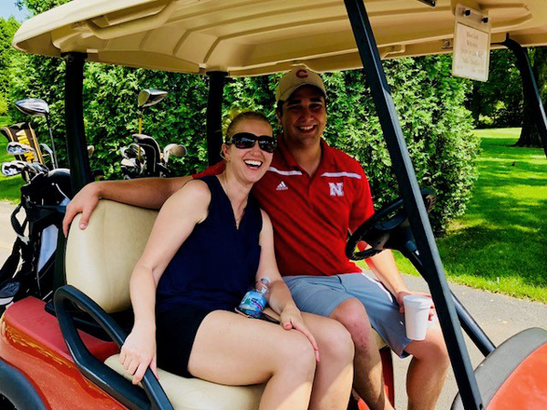 pair of golfers in a golf cart, smiling