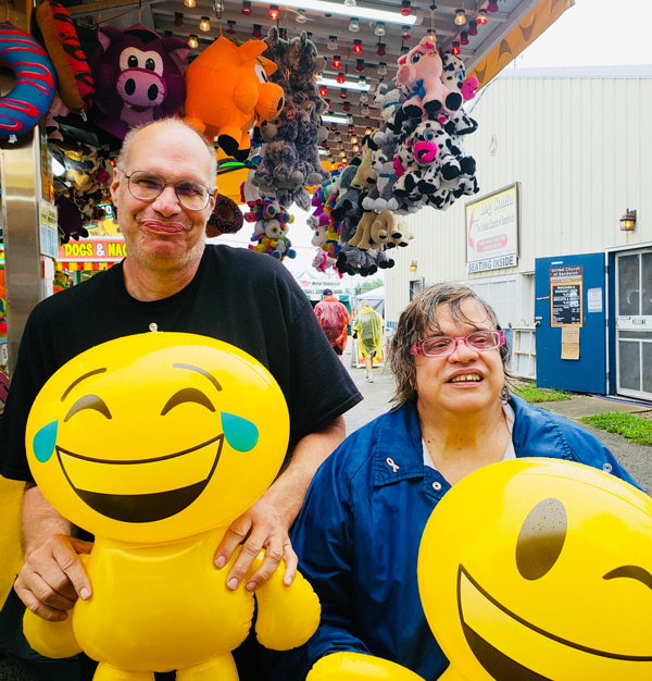 a pair of clients holding large emoji balloon prizes
