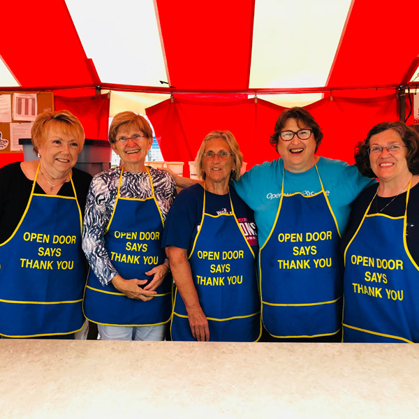 a group of fair volunteers pose in aprons